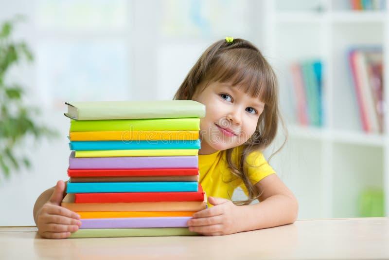 Smart ungeflickaförskolebarn med böcker royaltyfria foton