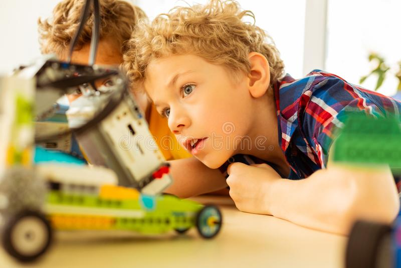 Smart upphetsad pojke som är nyfiken om robotteknik arkivfoton