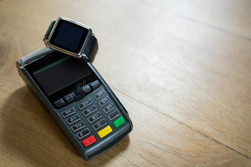 Smart watch and credit card reader on table in coffee shop. Close-up of smart watch and credit card reader on table in coffee shop stock photos