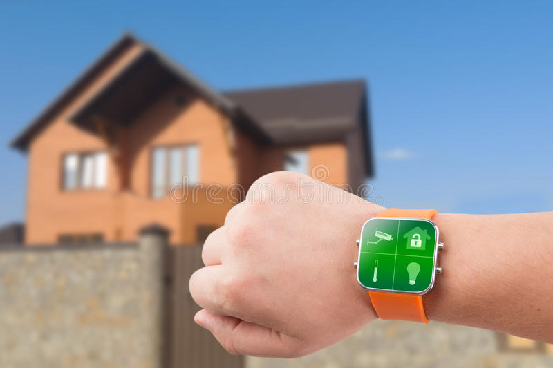 Smart watches with home security app on a hand on the building background. Smart watches with security app on a hand on the building background royalty free stock photos