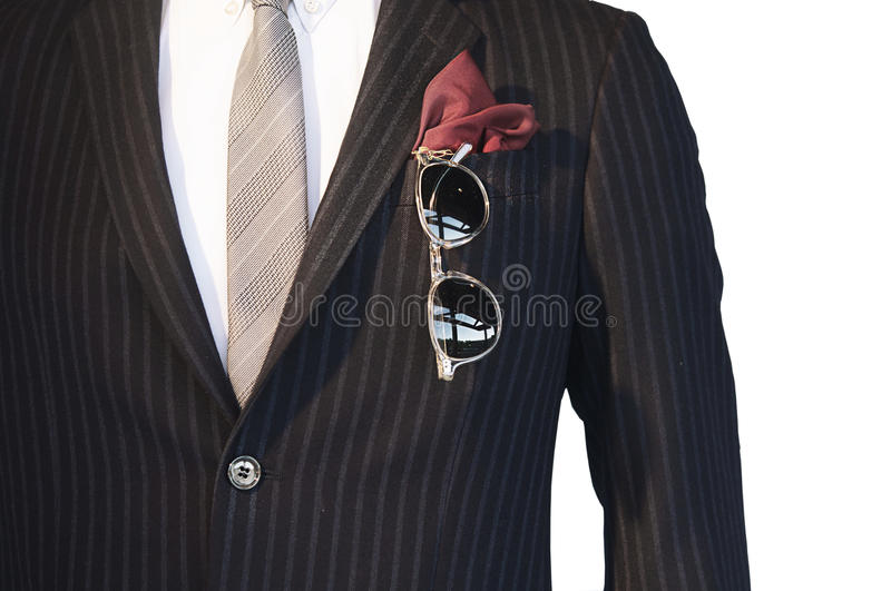 Smart well dressed man. Smart man wearing pin-stripe suit,shirt and tie with red hanker-chief and sunglasses in side pocket. Image isolated against white stock photography