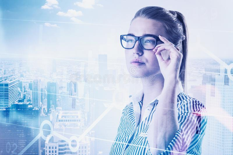 Smart woman trader in city, digital graph. Thoughtful blonde businesswoman in glasses standing over cityscape background with double exposure of digital graph stock images