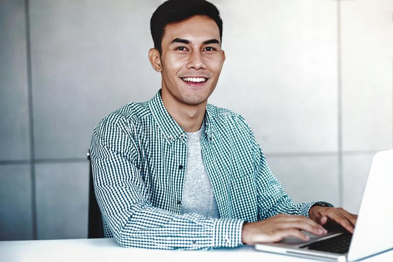 Smart Young Asian Businessman Working on Computer Laptop in Office. Happy Smiling Guy stock image