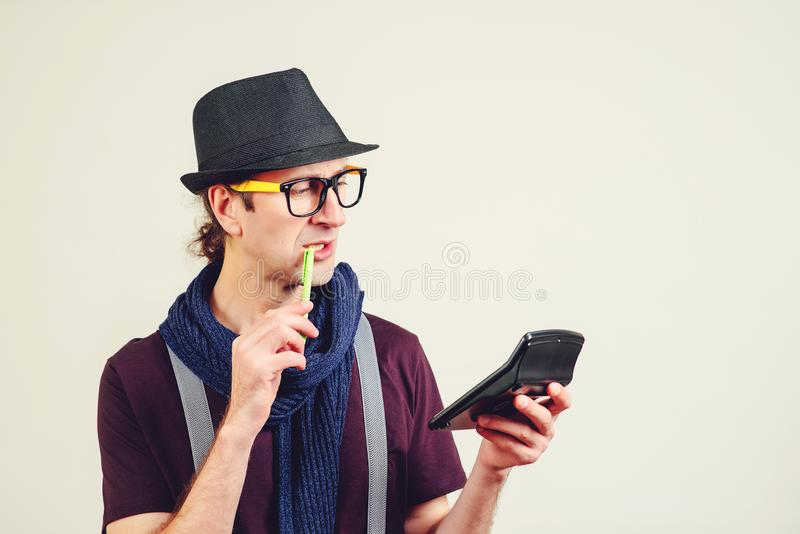 Smart young nerd holding calculator. Funny man in glasses doing accounting and calculating. Business, banking , education, people stock photography