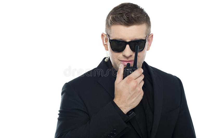Smart young security personnel communicating stock images