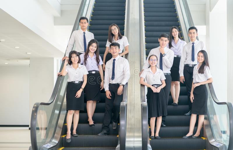 Smart young students standing together on escalator royalty free stock photography