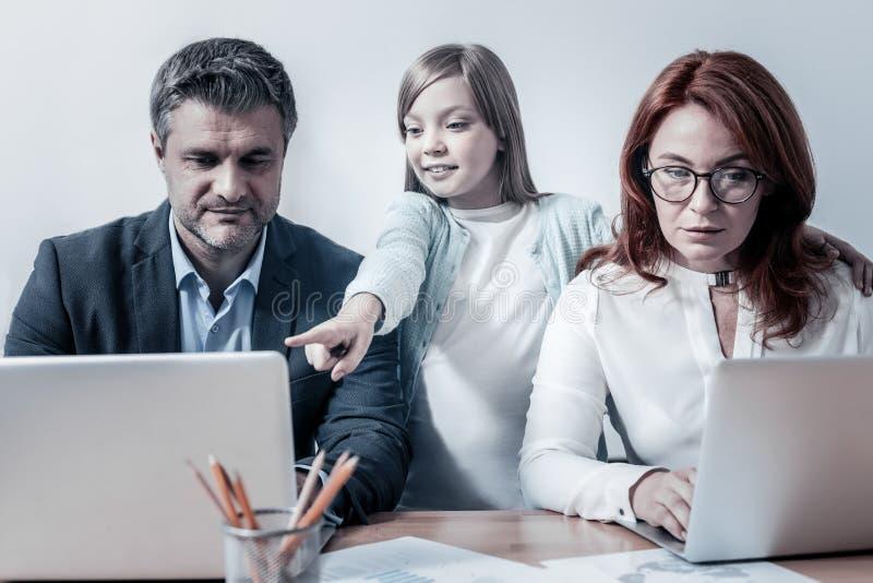 Smarta dotterportionföräldrar med arbete arkivbilder
