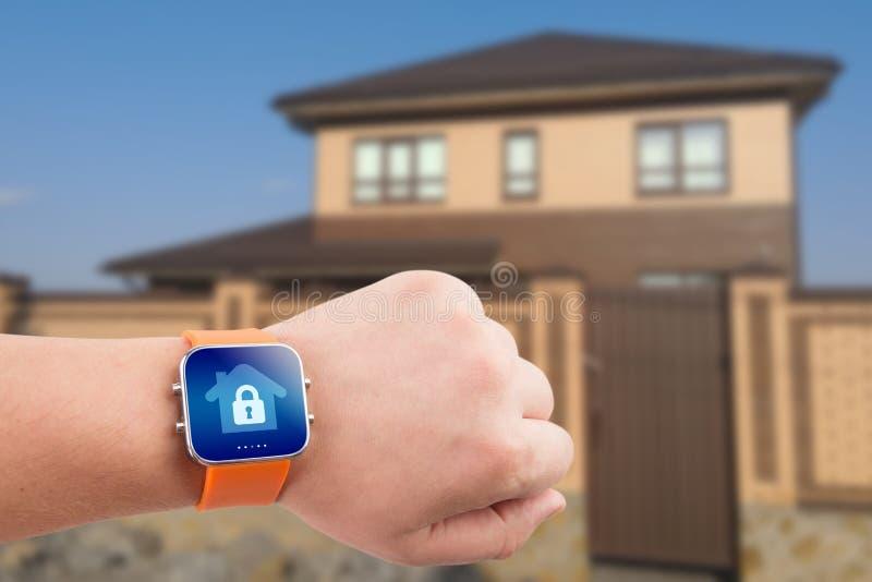 Smarta klockor med hem- säkerhet app på en hand på byggnadsbakgrunden royaltyfri foto