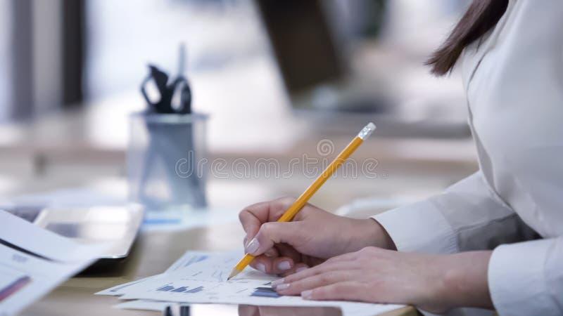 Smarta kvinnliga upptagna kontrollerande dokument för kontorsarbetare som gör anmärkningar på diagram royaltyfri bild