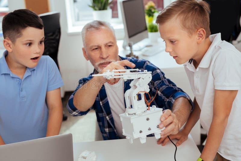 Smarta nyfikna pojkar som ser den moderna roboten royaltyfria bilder