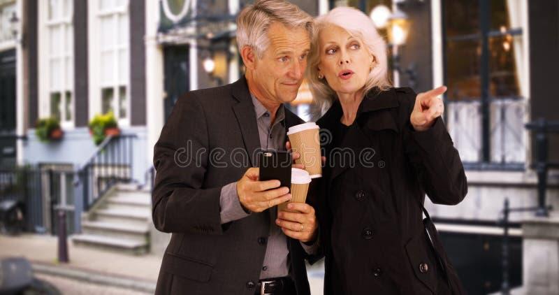 Smarta pensionärer som använder smartphonen för att finna deras väghem royaltyfria bilder