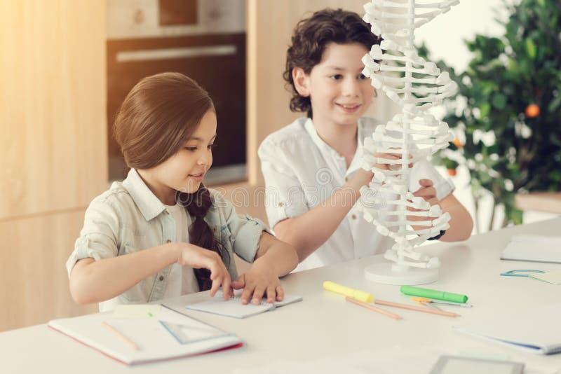 Smarta positiva barn som studerar biologi arkivbilder