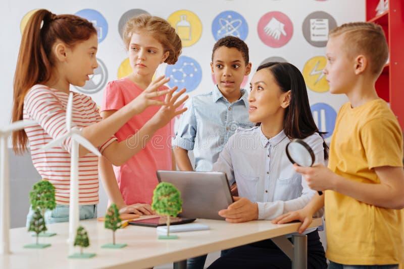 Smarta skolbarn som delar deras ekologi, projekterar idé med läraren arkivfoto