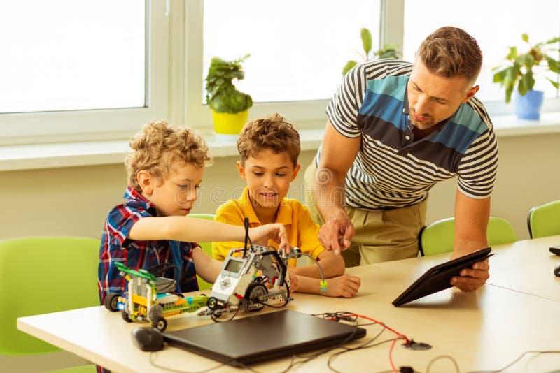 Smarta unga pojkar som tillsammans konstruerar en bilmodell arkivbild