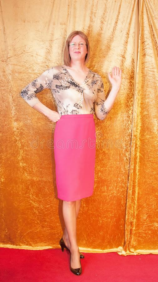 Smartly dressed Woman stood by curtain waving her hand. A casually dressed Woman wearing a pattern blouse and a pink pencil skirt stood by a curtain waving stock image