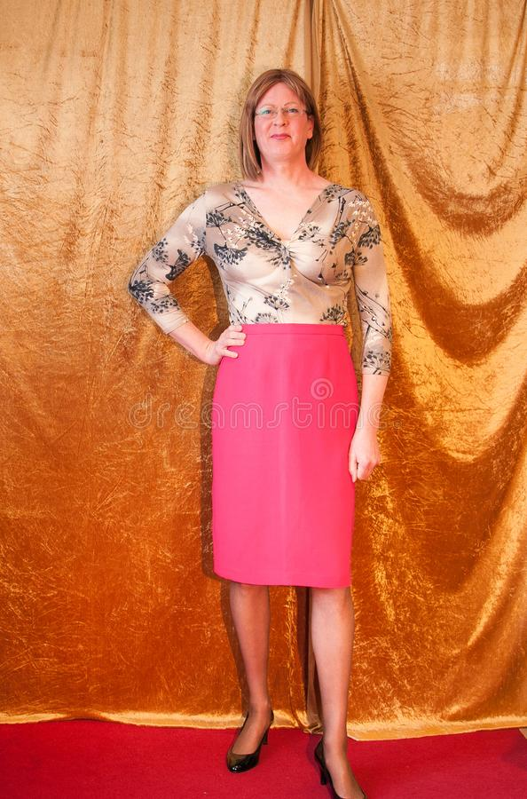 Smartly dressed Woman stood by curtain. A smartly dressed Woman wearing a pattern blouse and a pink pencil skirt stood by a curtain looking happy royalty free stock photo