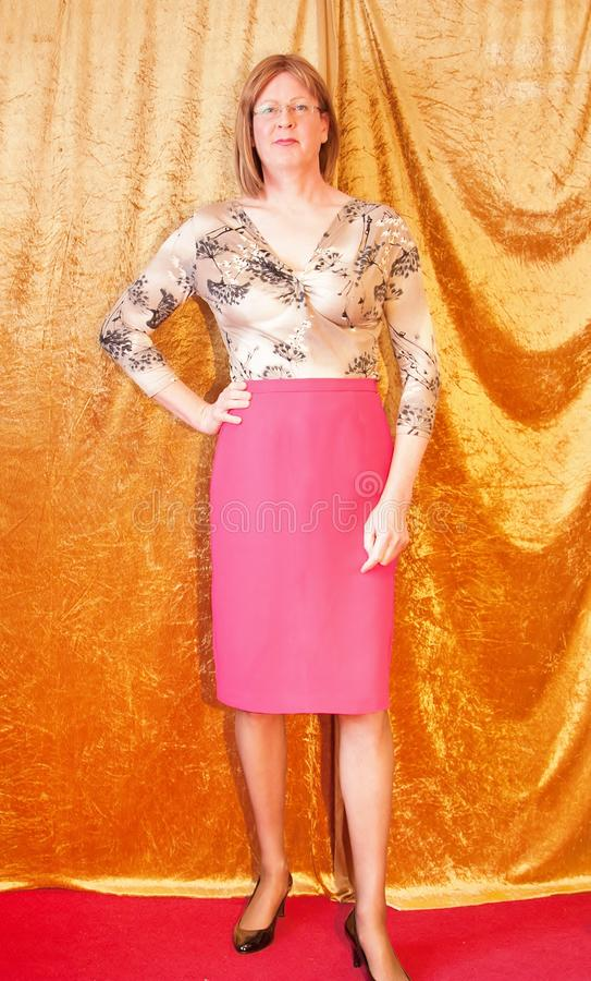 Smartly dressed Woman stood by curtain. A smartly dressed Woman wearing a pattern blouse and a pink pencil skirt stood by a curtain looking happy stock image