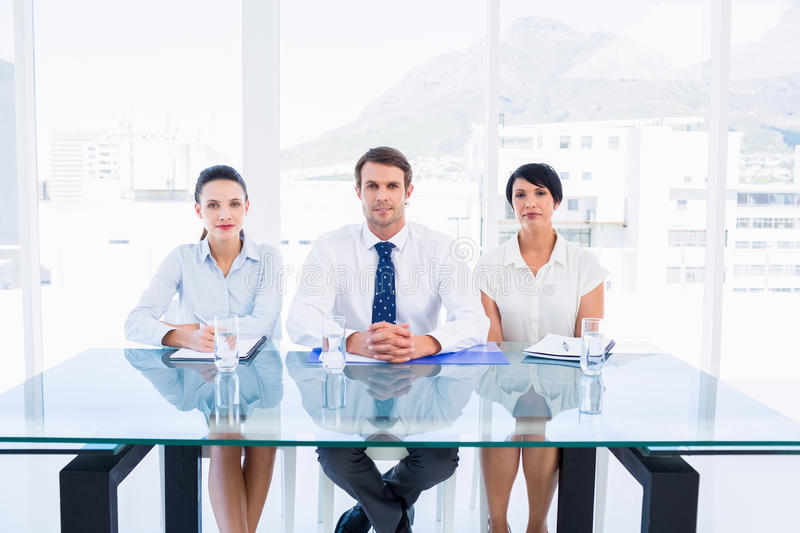 Smartly dressed young executives sitting at desk. Portrait of smartly dressed young executives sitting at desk in a bright office stock photo