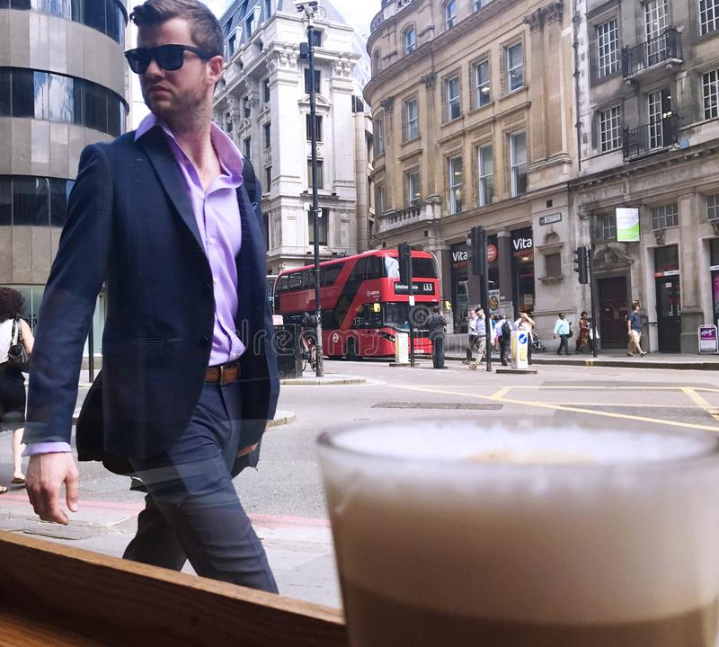 A smartly dressed young man looks at his own reflection in a coffee shop window in the City of London, UK. September 2017 stock photography