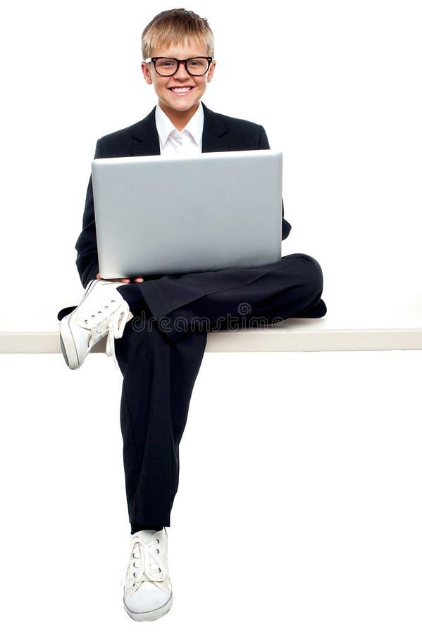 Smartly gekleed jong jong geitje dat aan laptop werkt royalty-vrije stock foto