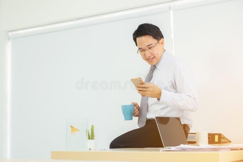 Smartphone à disposição do homem de negócios durante a café-ruptura que verifica e foto de stock royalty free