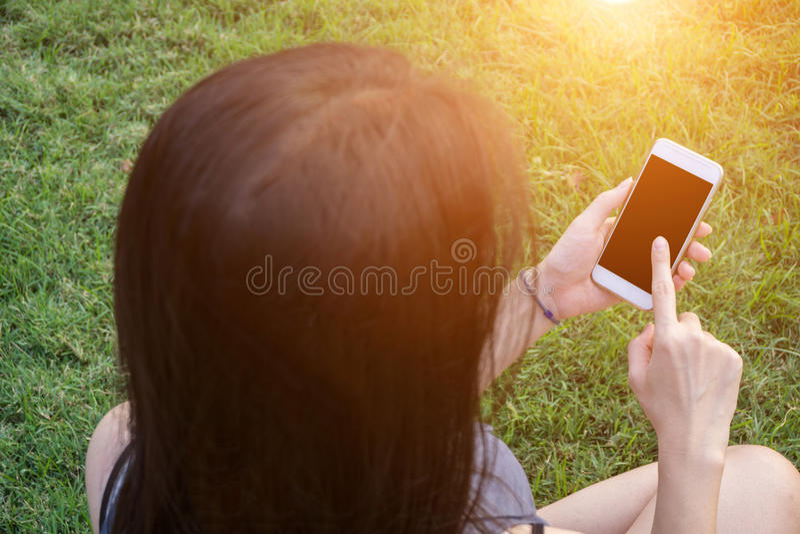 Smartphone émouvant de jeune femme sur l'herbe verte image stock