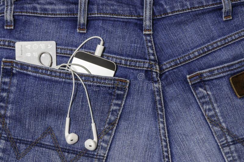 Smartphone, ακουστικά και πρόσβαση τραπεζικών καρτών στην πίσω τσέπη στο τζιν παντελόνι στοκ φωτογραφίες