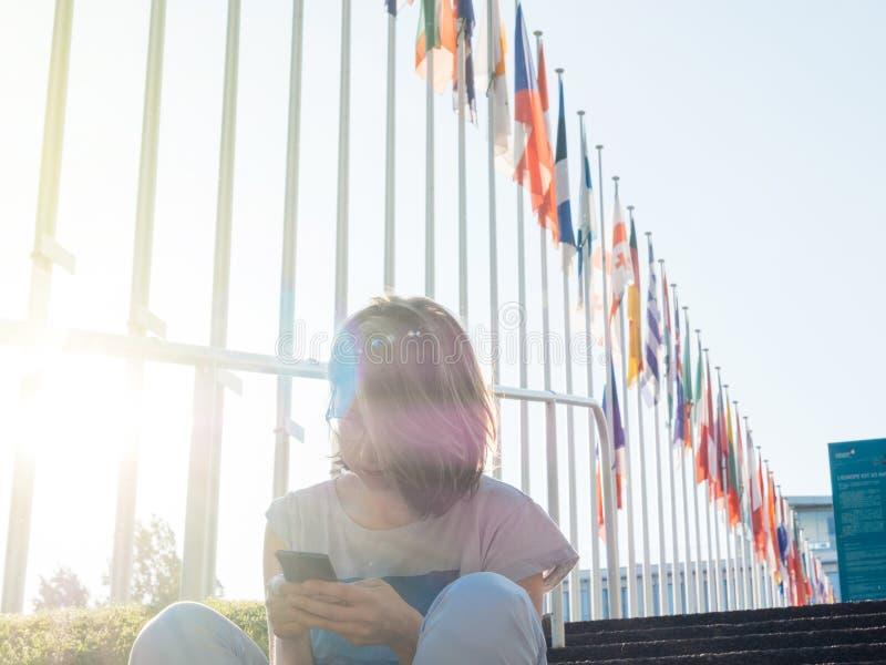 Smartphone ανάγνωσης γυναικών με την Ευρωπαϊκή Ένωση και οι Ηνωμένες σημαίες πετούν τον μισό-ιστό στοκ εικόνες
