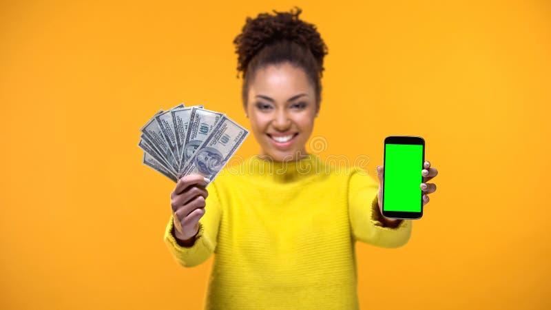 Γυναίκα αφροαμερικάνων που παρουσιάζει το smartphone και δέσμη των δολαρίων, μεταφορά χρημάτων στοκ φωτογραφία με δικαίωμα ελεύθερης χρήσης