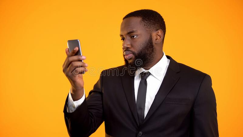 Smartphone εκμετάλλευσης επιχειρηματιών αφροαμερικάνων, κινητό οικονομικό εργαλείο, app στοκ εικόνες