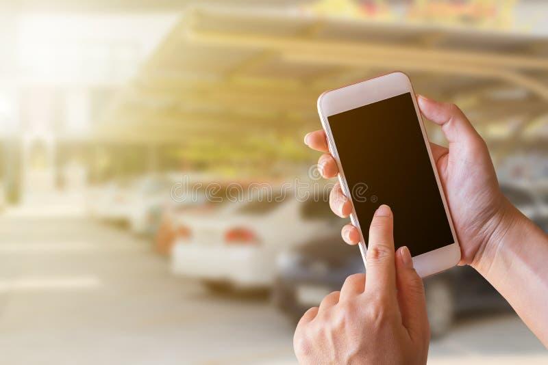 Smartphone εκμετάλλευσης επιχειρηματιών με το θολωμένο υπόβαθρο στοκ φωτογραφία