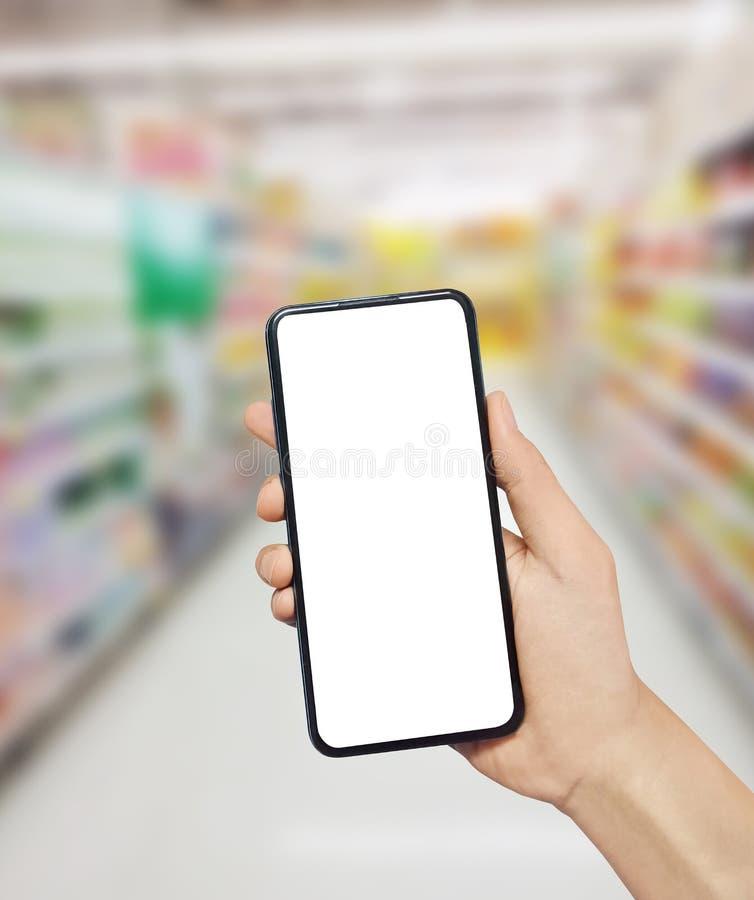 Smartphone εκμετάλλευσης χεριών ατόμων στην υπεραγορά r Κενή άσπρη οθόνη για το κείμενό σας στοκ εικόνα