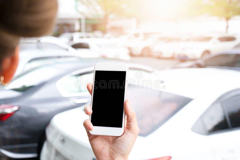 Smartphone εκμετάλλευσης χεριών με τη μαύρη οθόνη στο υπαίθριο σταθμό αυτοκινήτων στοκ εικόνες με δικαίωμα ελεύθερης χρήσης