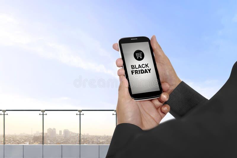 Smartphone εκμετάλλευσης χεριών με το μαύρα κείμενο Παρασκευής και το κάρρο αγορών στοκ εικόνες
