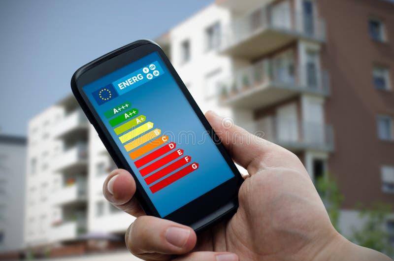 Smartphone εκμετάλλευσης ατόμων με το διάγραμμα ενεργειακής αποδοτικότητας στοκ εικόνα
