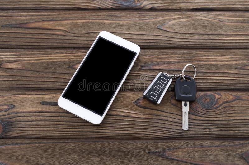 Smartphone, κλειδιά αυτοκινήτων στο υπόβαθρο στοκ φωτογραφία