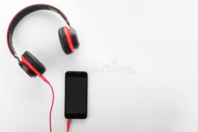 Smartphone με τα ακουστικά στο άσπρο υπόβαθρο, τοπ άποψη στοκ φωτογραφία με δικαίωμα ελεύθερης χρήσης