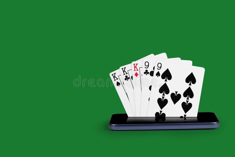 smartphone με τις κάρτες πόκερ, καρτών παιχνιδιών πλήρης βασιλική επίπεδη απεικόνιση χαρτοπαικτικών λεσχών εμβλημάτων σε απευθεία στοκ φωτογραφίες