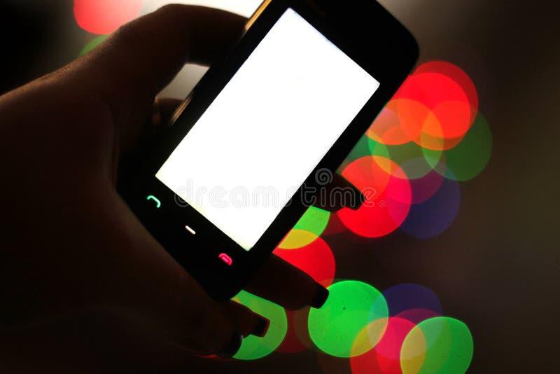 Smartphone στο χέρι, bokeh υπόβαθρο στοκ εικόνα