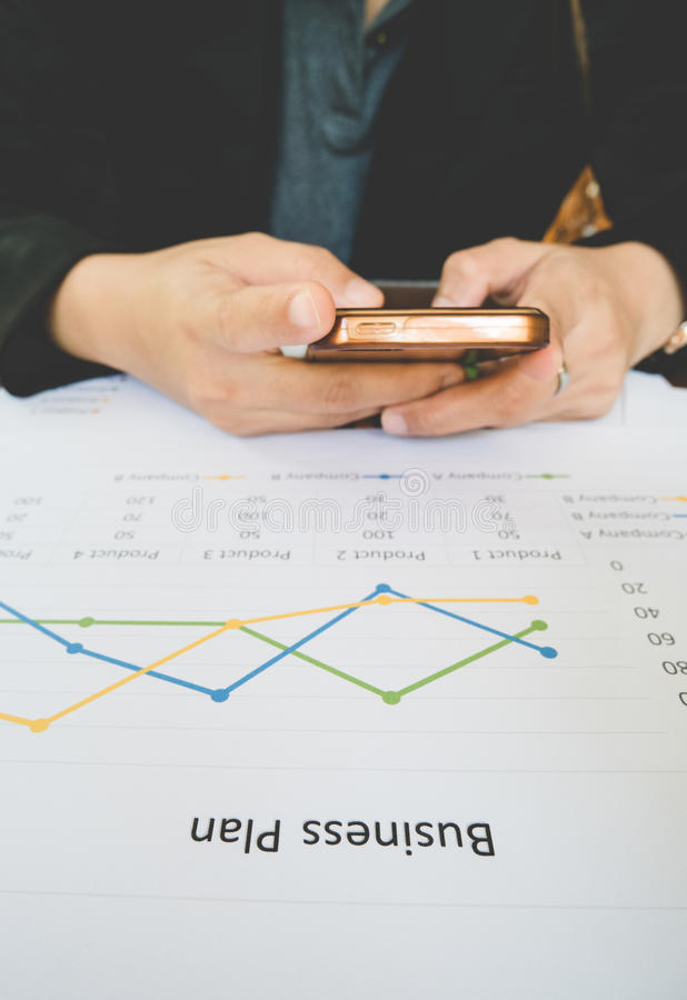 Smartphone χρήσης γυναικών εργασίας για την εργασία με την επιχειρησιακή περίληψη ή την έκθεση επιχειρηματικών σχεδίων με τα διαγ στοκ φωτογραφία
