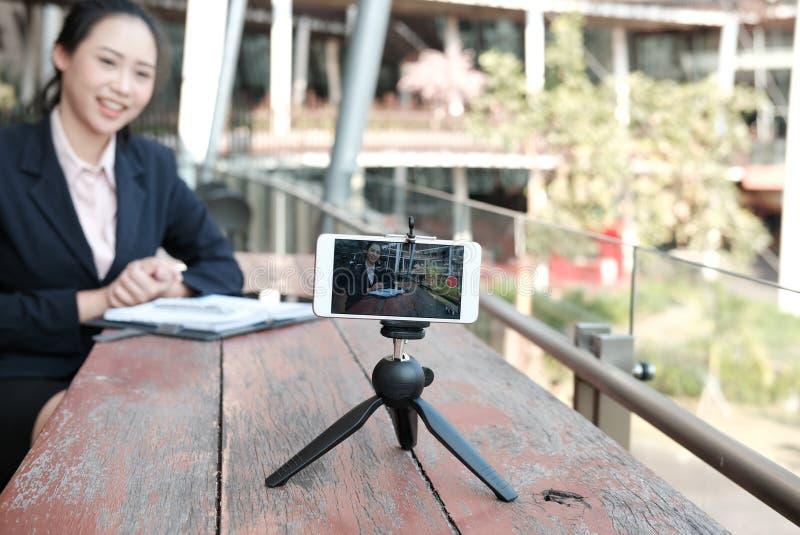 Smartphone χρήσης επιχειρηματιών για τη on-line ζωντανή ροή γυναίκα σχετικά με στοκ φωτογραφίες με δικαίωμα ελεύθερης χρήσης