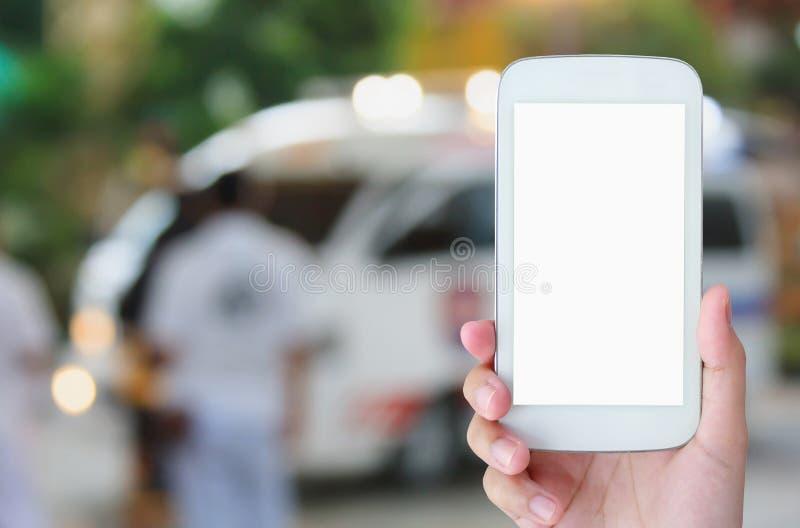 Smartphone владением руки с машиной скорой помощи стоковое изображение