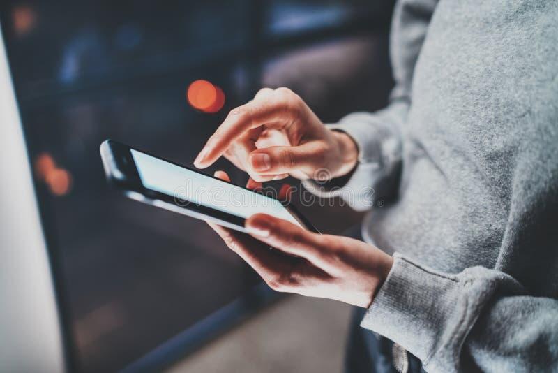 Smartphone держа в руках женщины Экран женских пальцев касающий белый пустой Горизонтальная, запачканная предпосылка стоковая фотография rf