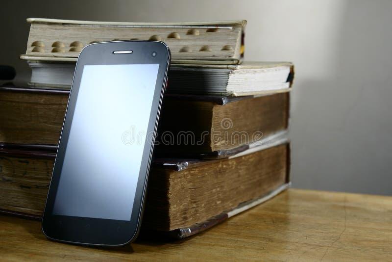 Smartphone или phablet и старые книги стоковые фотографии rf
