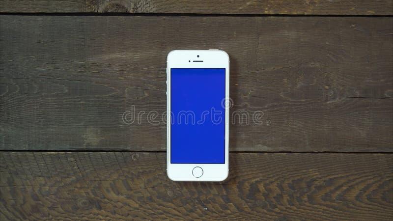 Smartphone руки ударов левый с голубым экраном стоковое изображение
