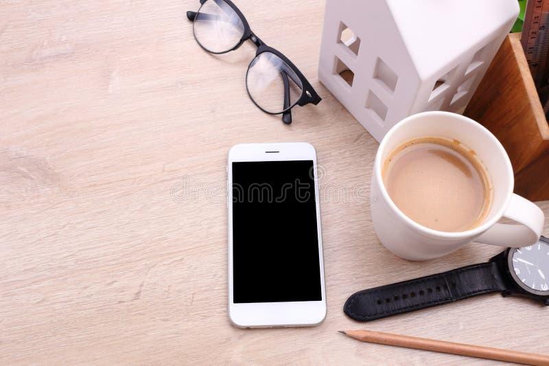 Smartphone, стекла и канцелярские товары пустого экрана на деревянном b стоковые фото
