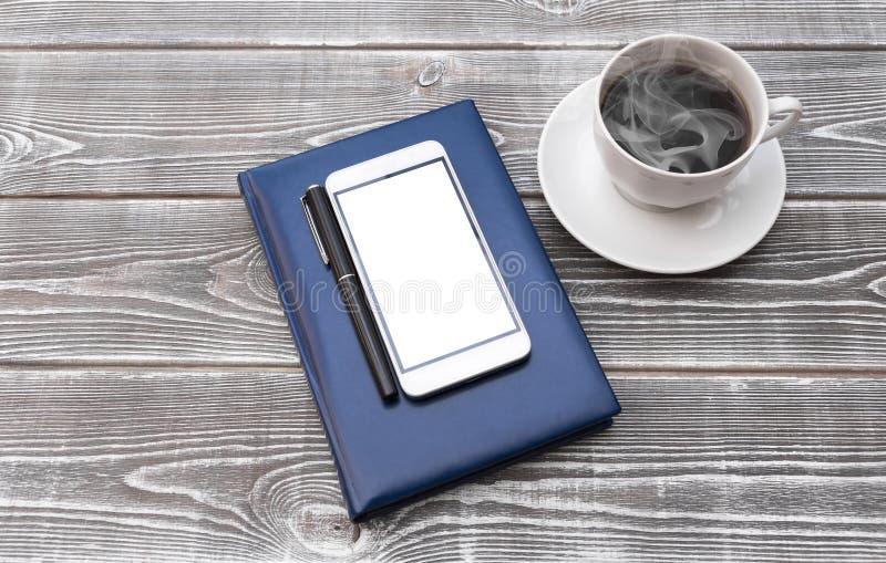 Smartphone с ручкой на тетради стоковое фото