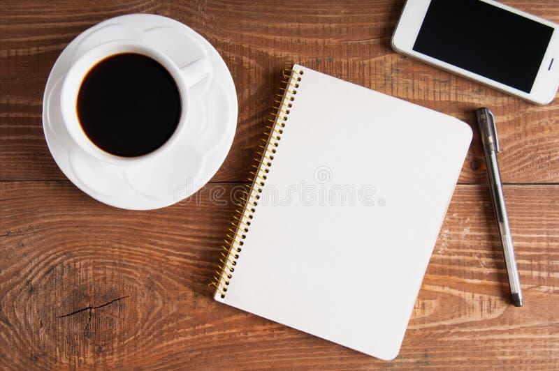 Smartphone с тетрадью и чашкой кофе на деревянной предпосылке стоковые фото