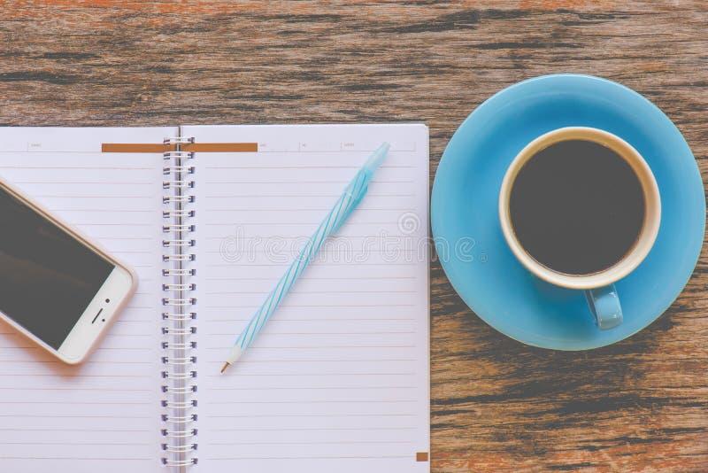 Smartphone с тетрадью и чашкой сильной голубой кофейной чашки стоковое фото