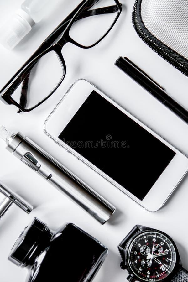 Smartphone, электронная сигарета и взгляд сверху аксессуаров ` s людей стоковая фотография